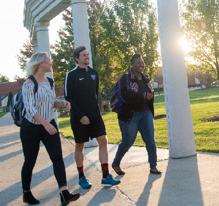 Two female and one male student walking across the campus sidewalk. The sun is flaring light around a pillar in the background.