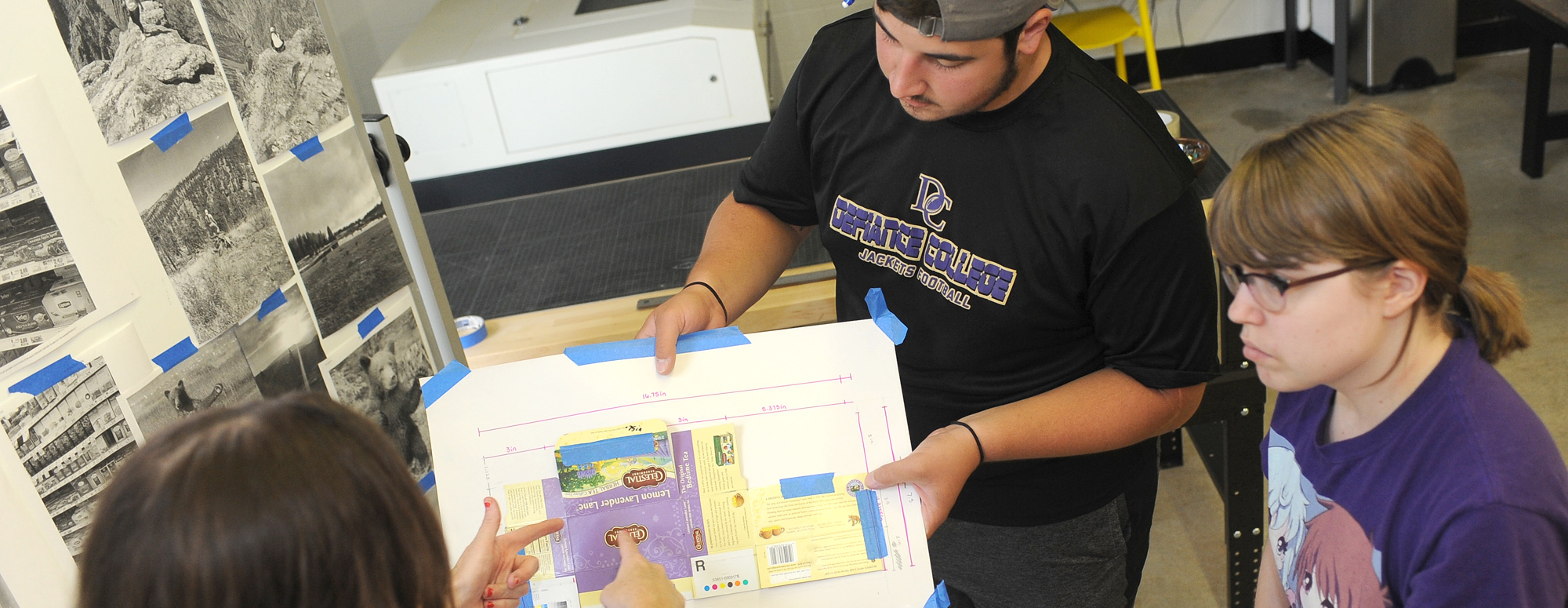 two students looking at a design project on a board