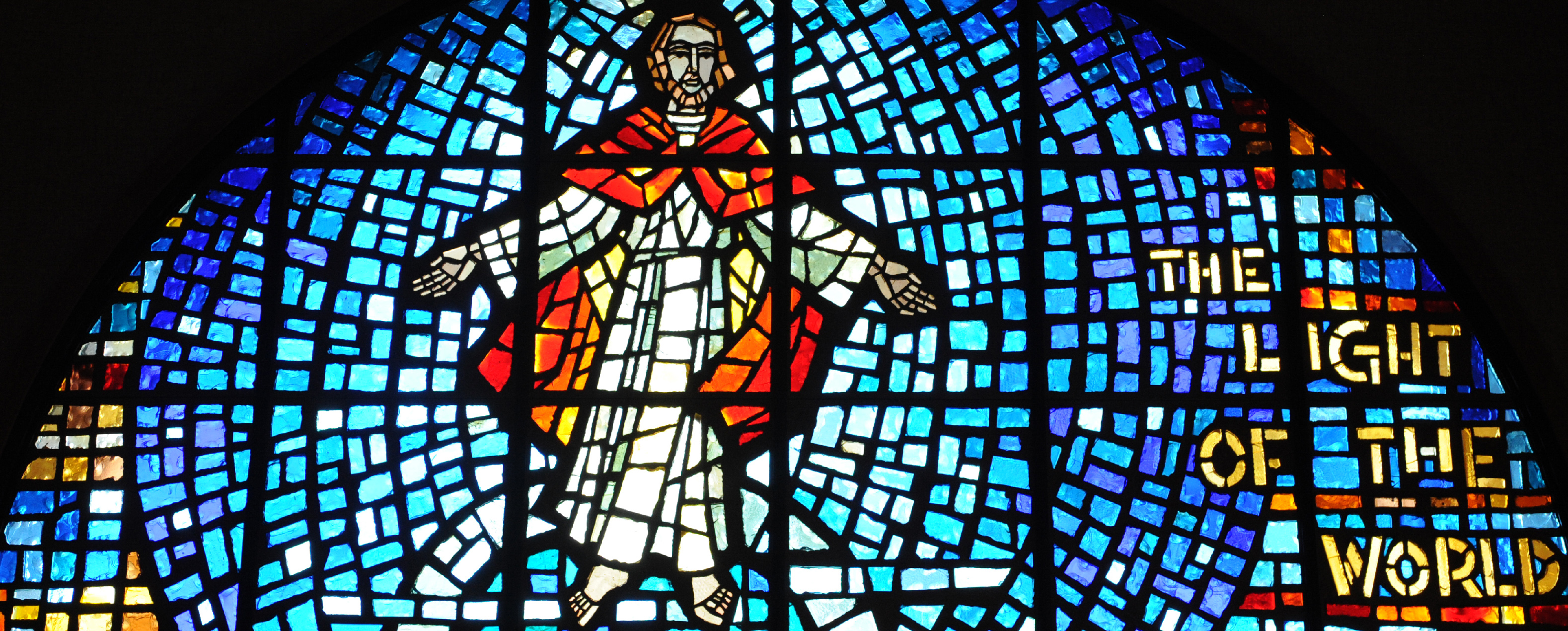 Stained glass window featuring Jesus in white and red robes, surrounded by a blue background. Yellow words on the right side say: The light of the world.