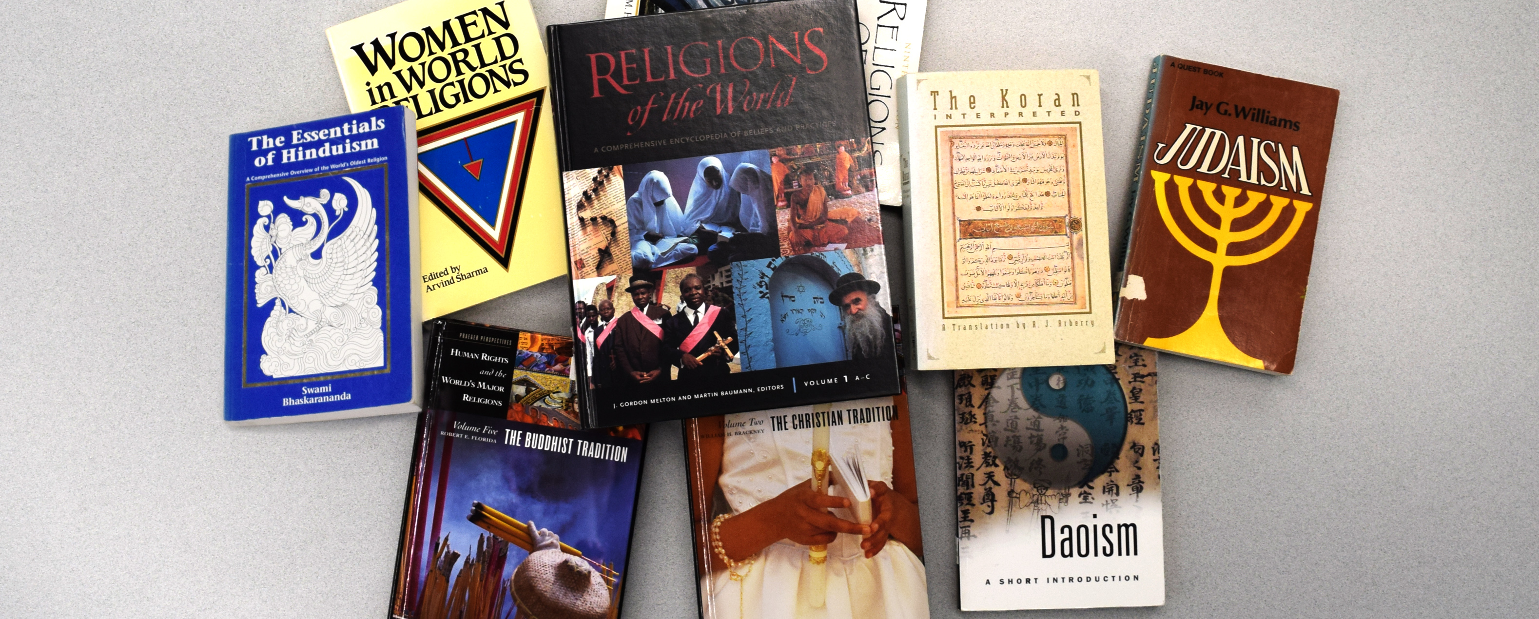 Nine books on various world religions spread out on a table top.