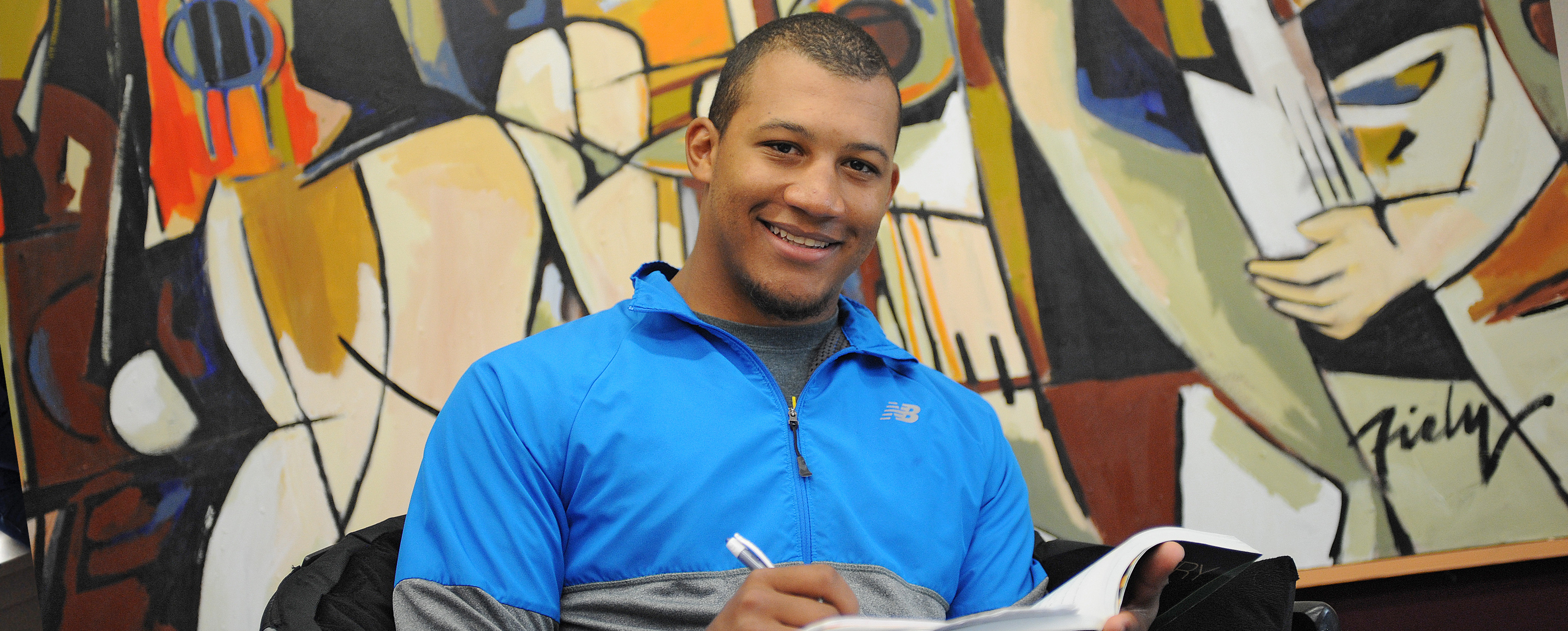 Student sitting in front of a large painting and writing in a book. He smiles at the camera.