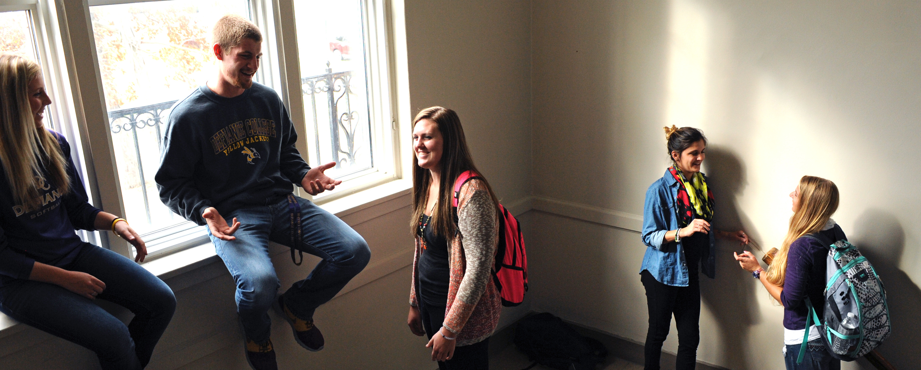 Five students gathered and speaking together in a large stairwell. Light from the big window in the background highlights the room.