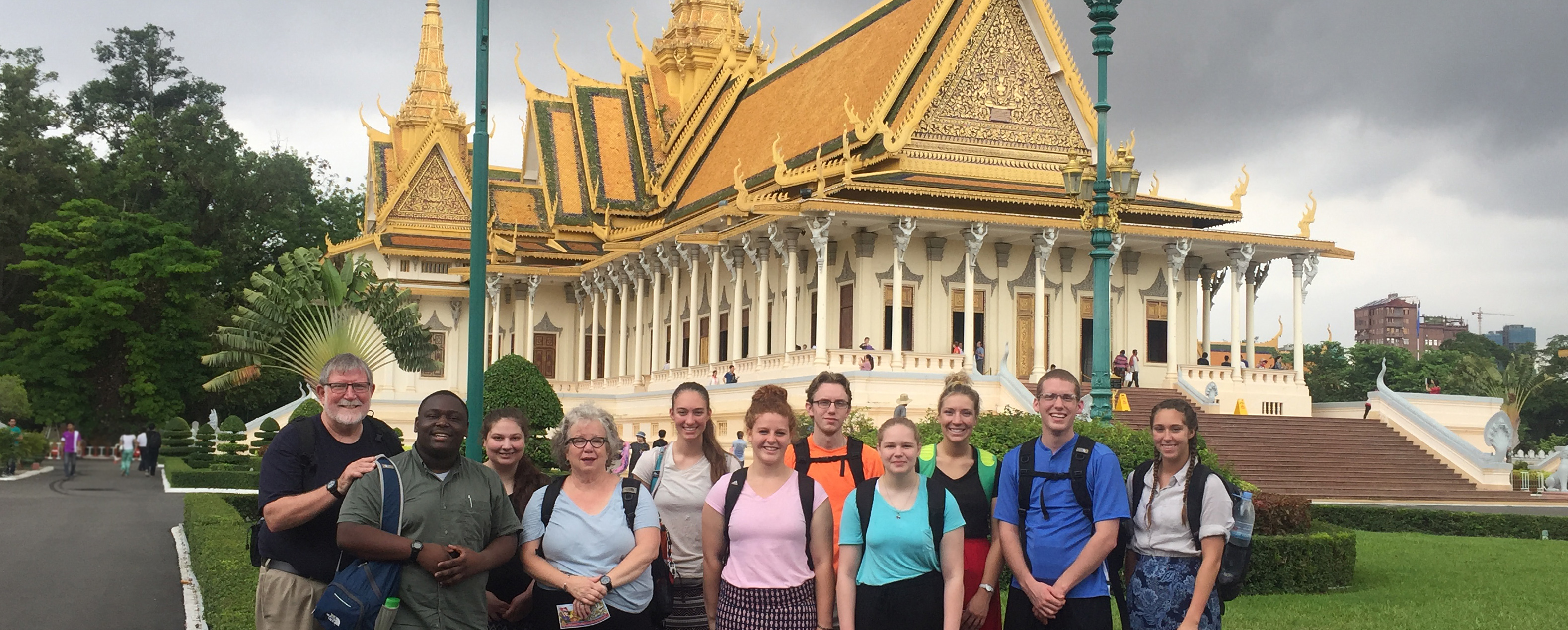 11 individuals from Defiance College wearing all different and brightly colored shirts with backpacks. They are gathered together to smile at the camera, standing in front of a large pale yellow building with a tall golden roof. The building is the Silver Pagoda in Cambodia.