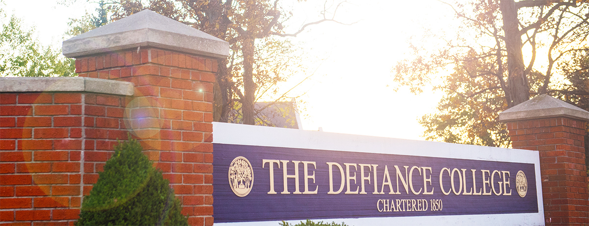 Purple and white sign with gold letters framed by brick posts reading: The Defiance College, chartered 1850