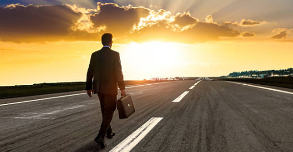 Man in business attire with a briefcase walking on a road into a sunrise