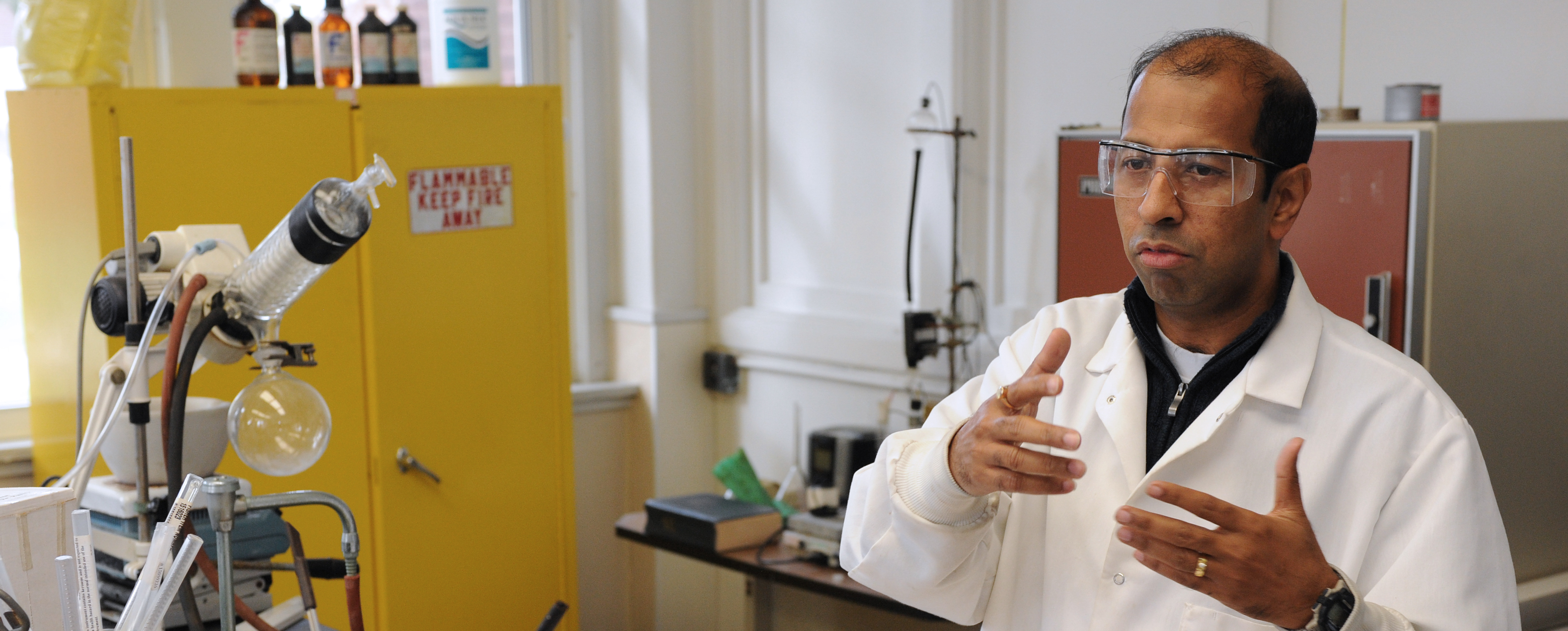 Professor Dutta wearing goggles and a white lab coat, standing around lab equipment and gesturing with his hands as he speaks.