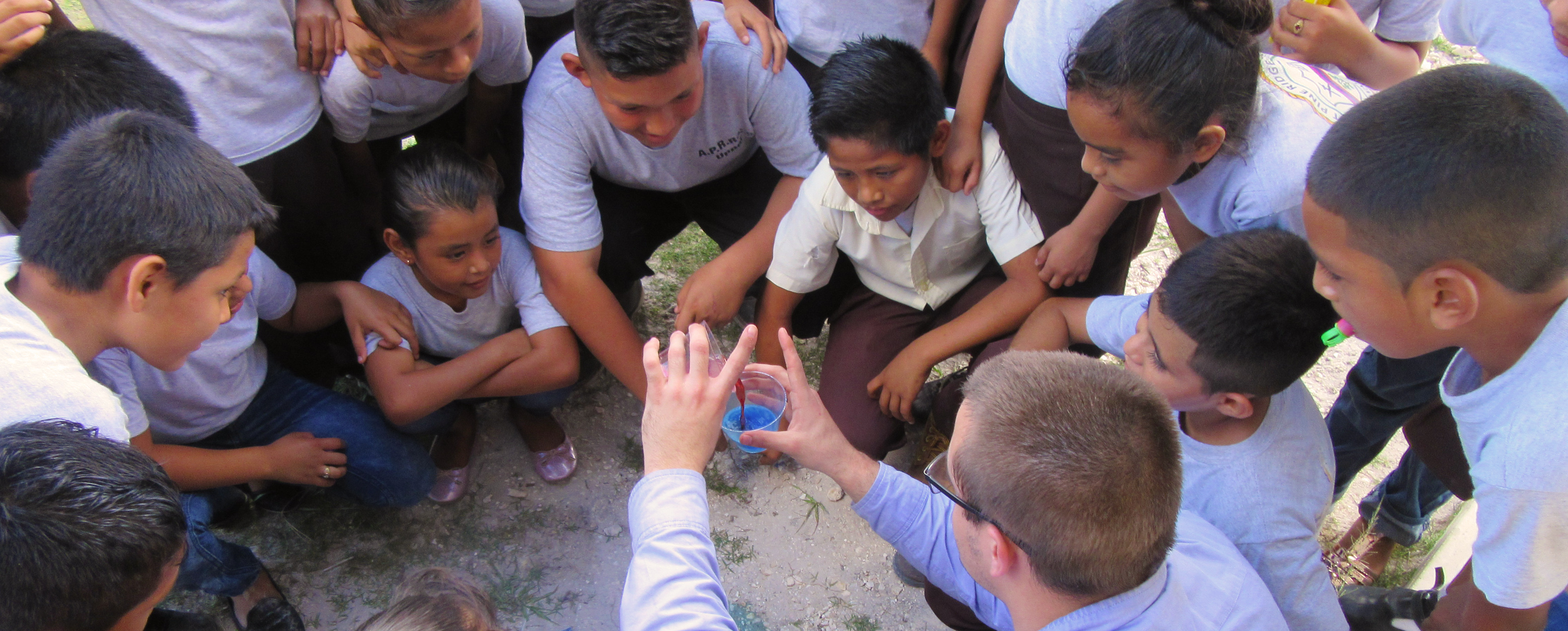 14 kids of varying ages gathered in a circle around a young man who is holding a cup filled with blue liquid.