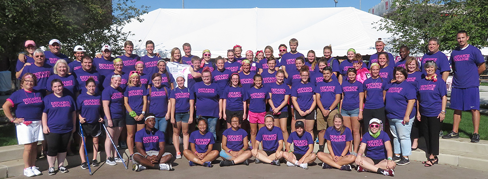 Large group of students and staff at Race for the Cure in purple DC shirts