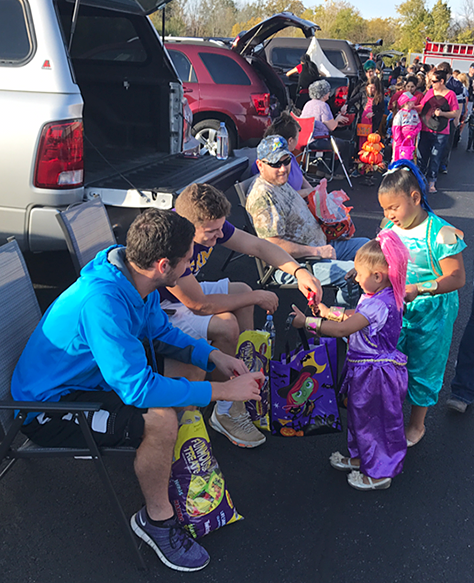Students giving trick or treat candy to kids in costumes