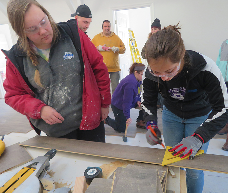 2 female students using carpentry tools. 4 students are moving in the background and 1 supervisor is watching from the middle of the image.