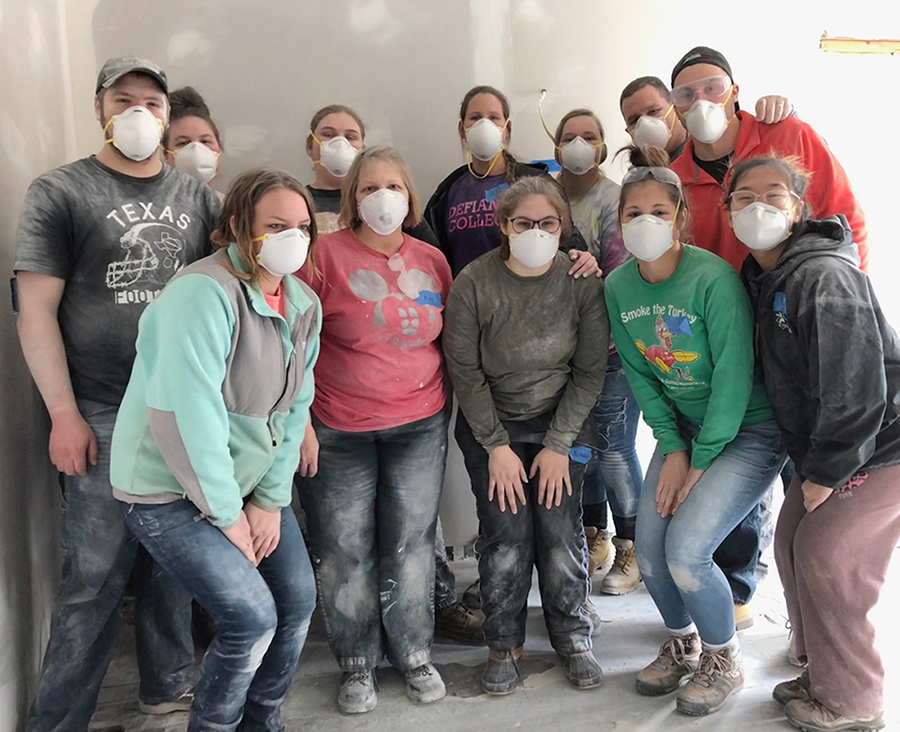 12 individuals standing in a line facing the camera, wearing white construction face masks. Their clothes are dirty from working on a house.