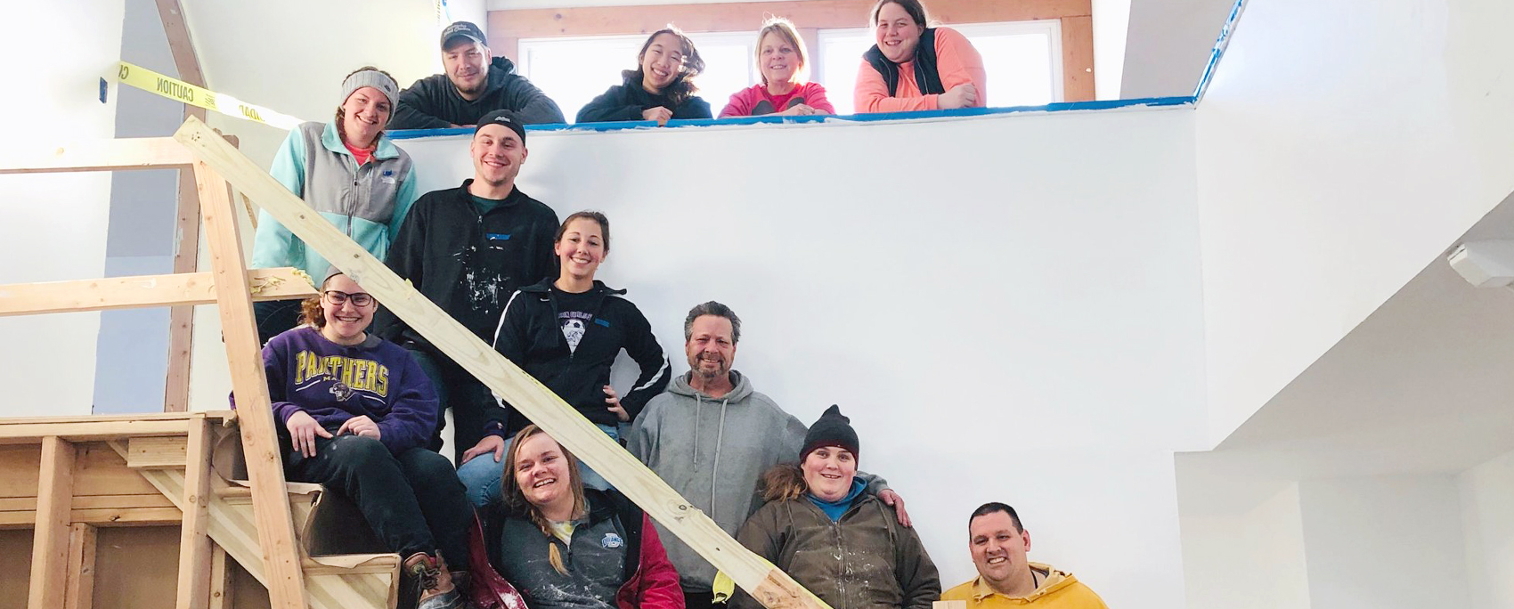12 individuals in various colors of jackets and hoodies all smiling and standing on stairs and an upstairs landing in a home construction.