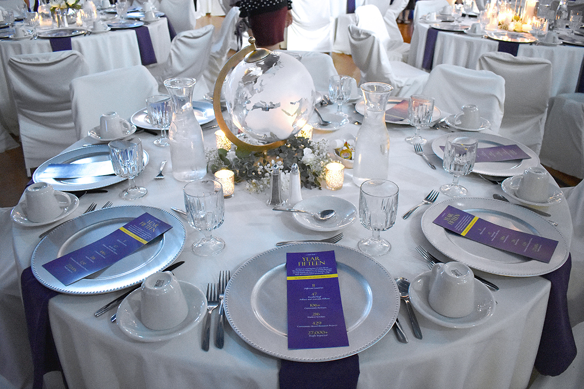 Table set up with white table cloth, purple banners, plates, glasses, silverware, and centerpiece.