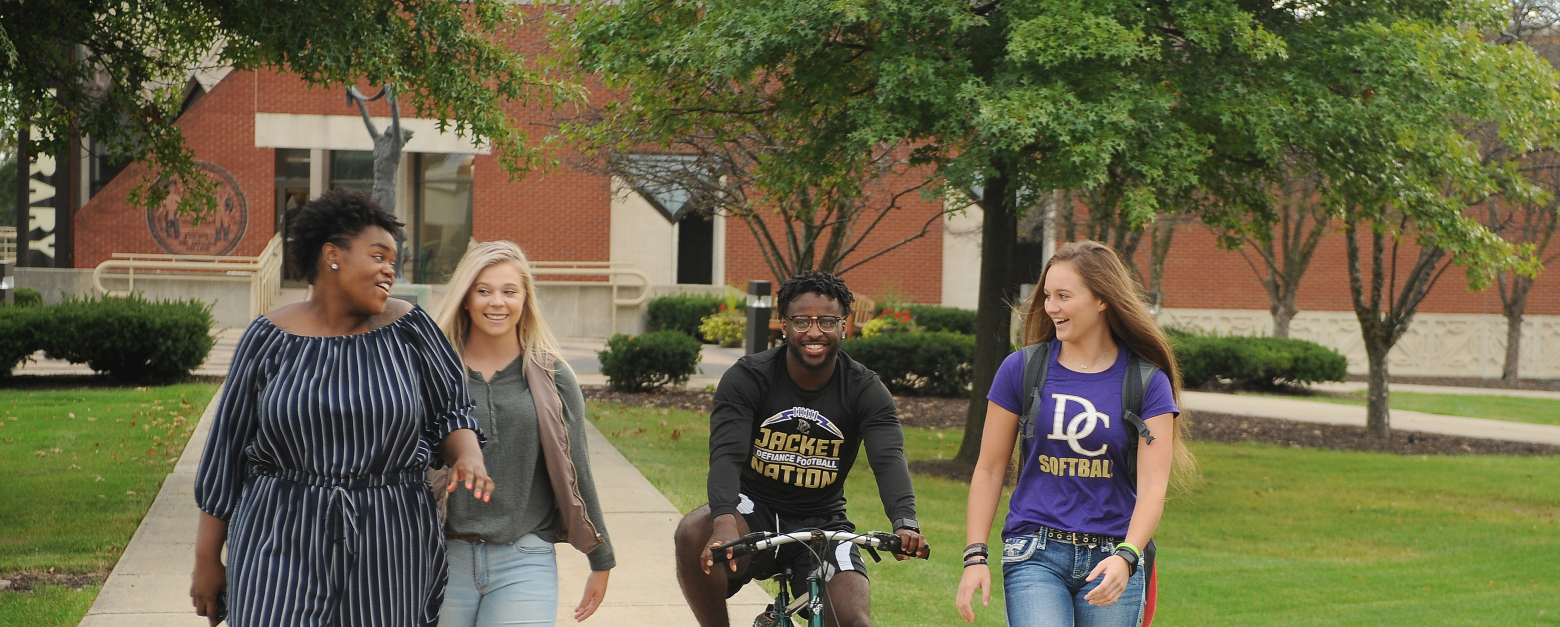 Three female students walking on a campus sidewalk with a male student on a bike. All are actively talking with each other and smiling.