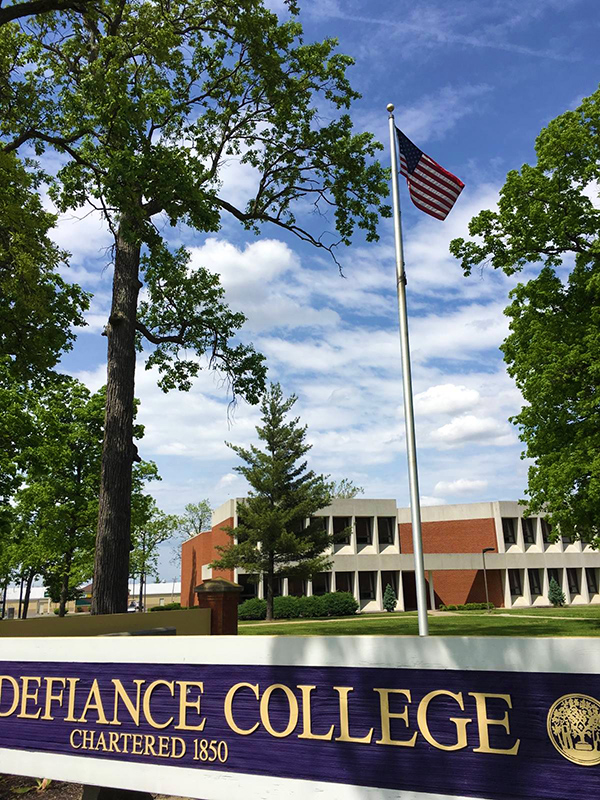 American flag flying against a blue sky in front of a Defiance College sign